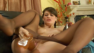 Pigtailed girl in sleek suntan pantyhose messing with two huge jelly toys videos